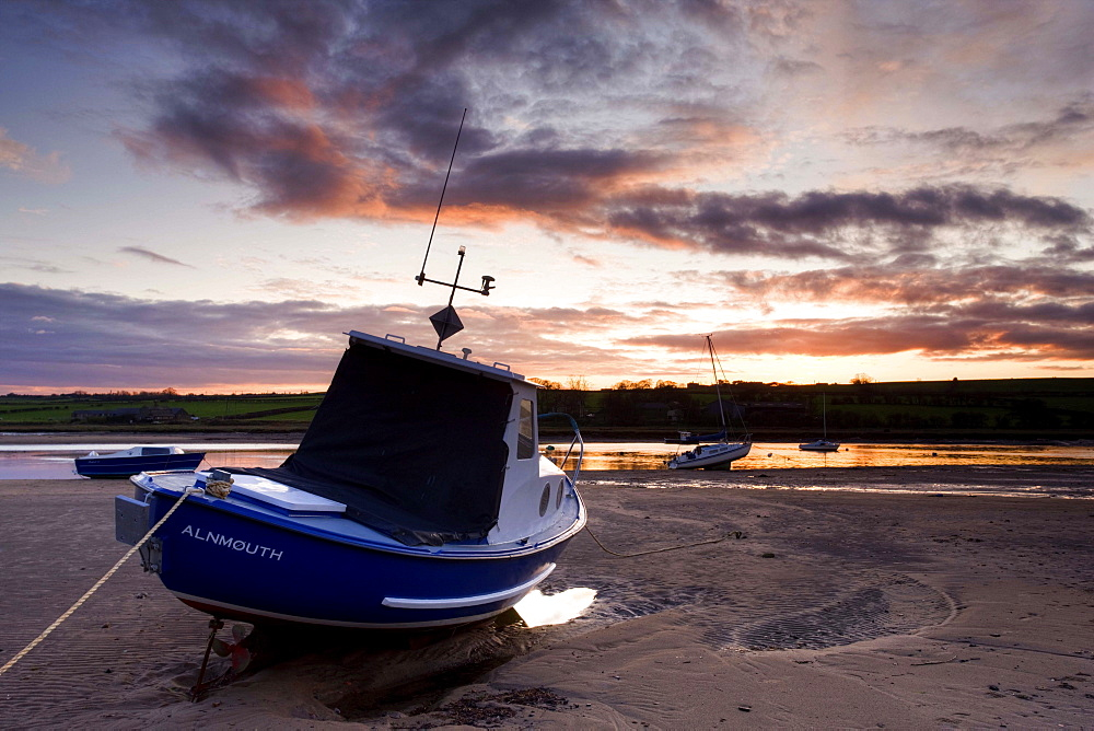 Fishing boat on the Aln Estuary at twilight, low tide